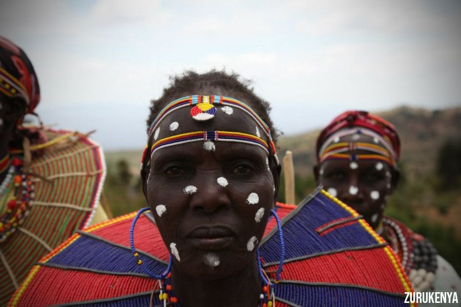 A closeup shot of Kalenjin Tribe member with white fot paints on the face and colorful lines, and a blue and red traditional necklace | Flash mctours and Travel