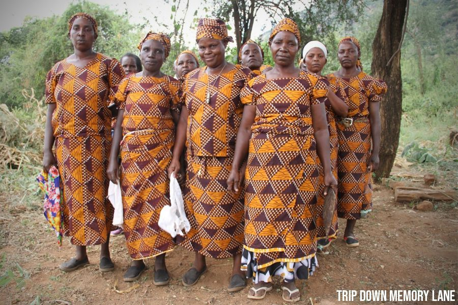 Kamba Tribe's women members standing infront of the camera wearing their patterned colorful clothes and head gear of orange and brown | Flash mctours and Travel