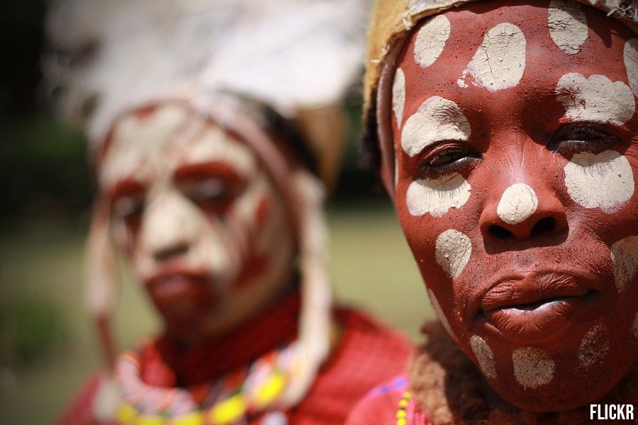 Close up shot of the two members of Kikuyu Tribe with a red paint and white dots on the face wearing yellow necklaces and traditional head gears | Flash Mctours and Travel